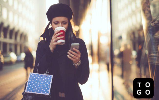 スマホを触りながらコーヒーを飲む女性
